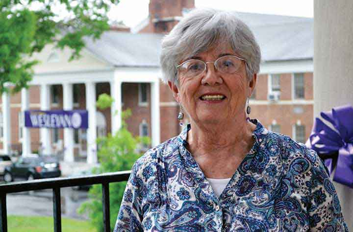 Alumnae Julia Ketcham on outside porch of Candler with Olive Swann Building behind her.