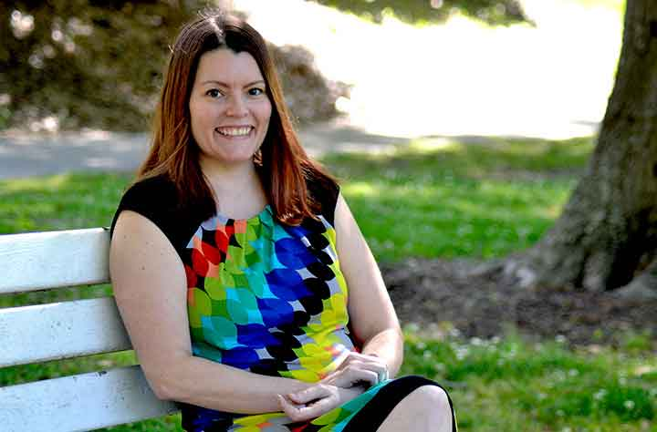 Brooke Bennett-Day sitting on bench in the college quad