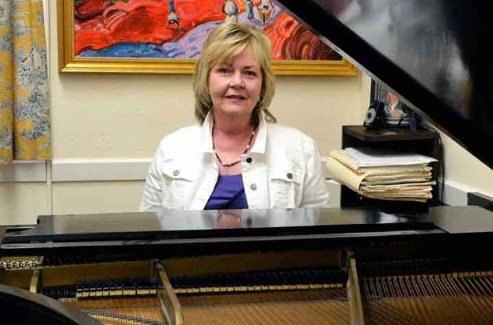 Faculty member Ellen Hanson sits at her piano in her office