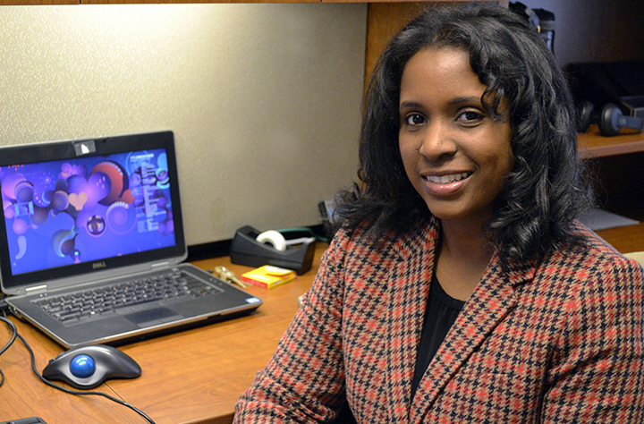 Faculty member Line Valerie Goss smiles at the camera sitting at her deck with her laptop in the background.