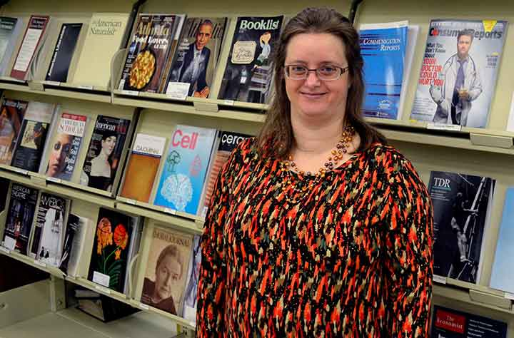 Melissa Roberts standing in front of books in the Willet Library