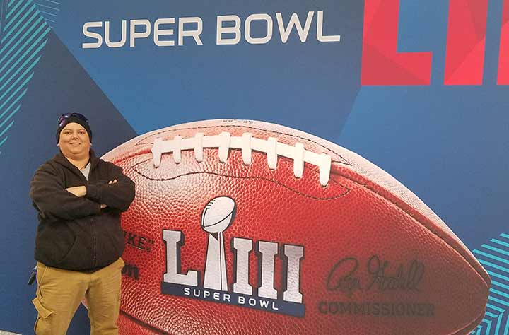 Mo stands in front of Super Bowl sign