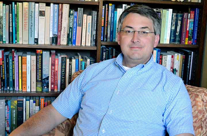 Nicholas J. Steneck sitting in his office in front of bookcase