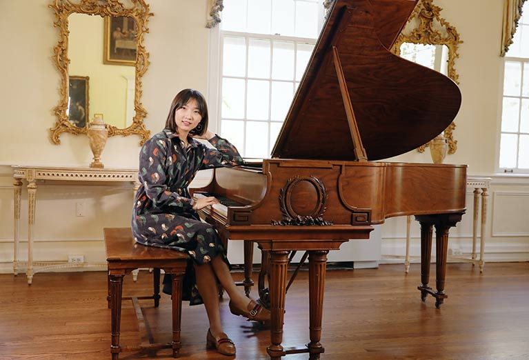 Valentina Huang sits at the piano in the Burden Parlor on campus.