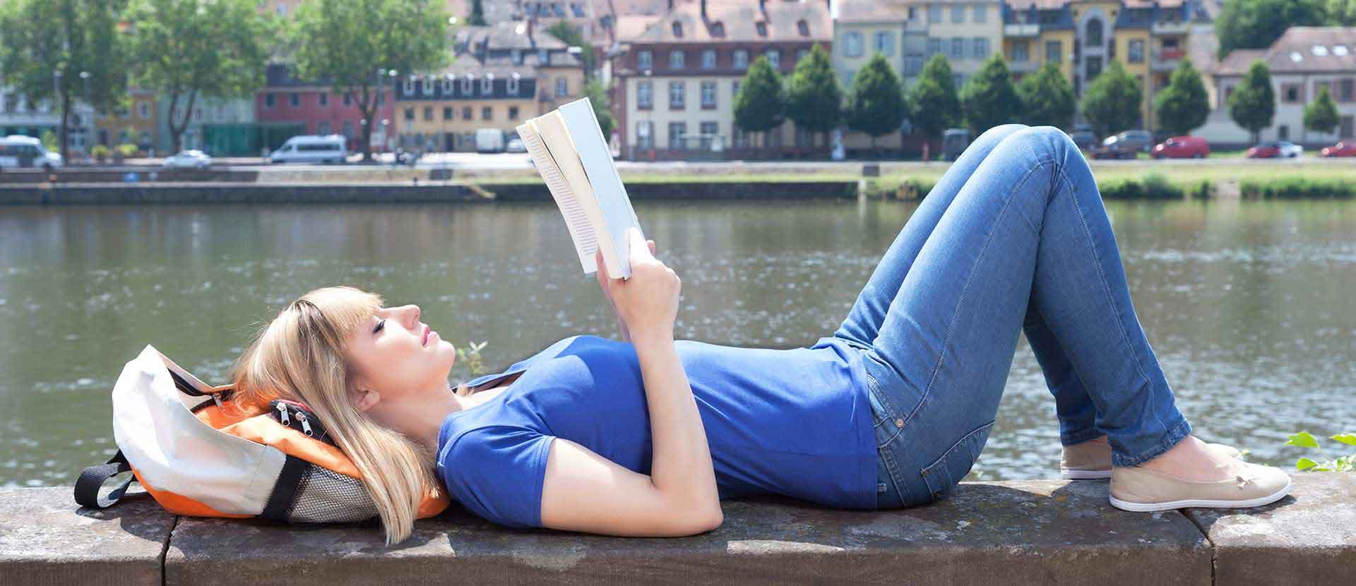 Student reads a book by the lake while studying abroad