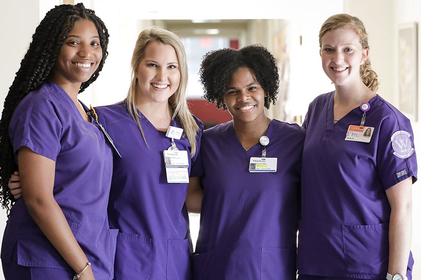 Four Nursing students in Munroe Science Center hall.