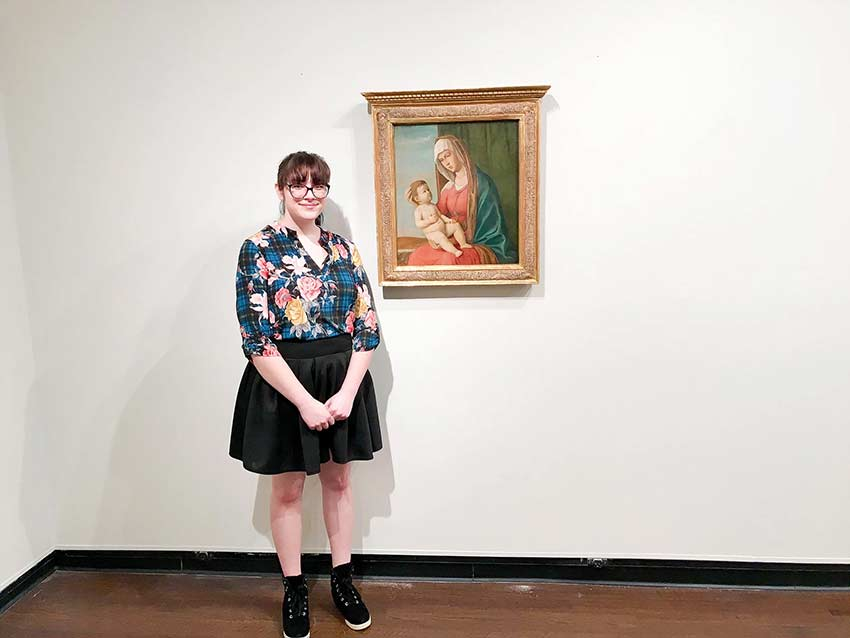 Art History major stands in front of painting in Wesleyan collection.