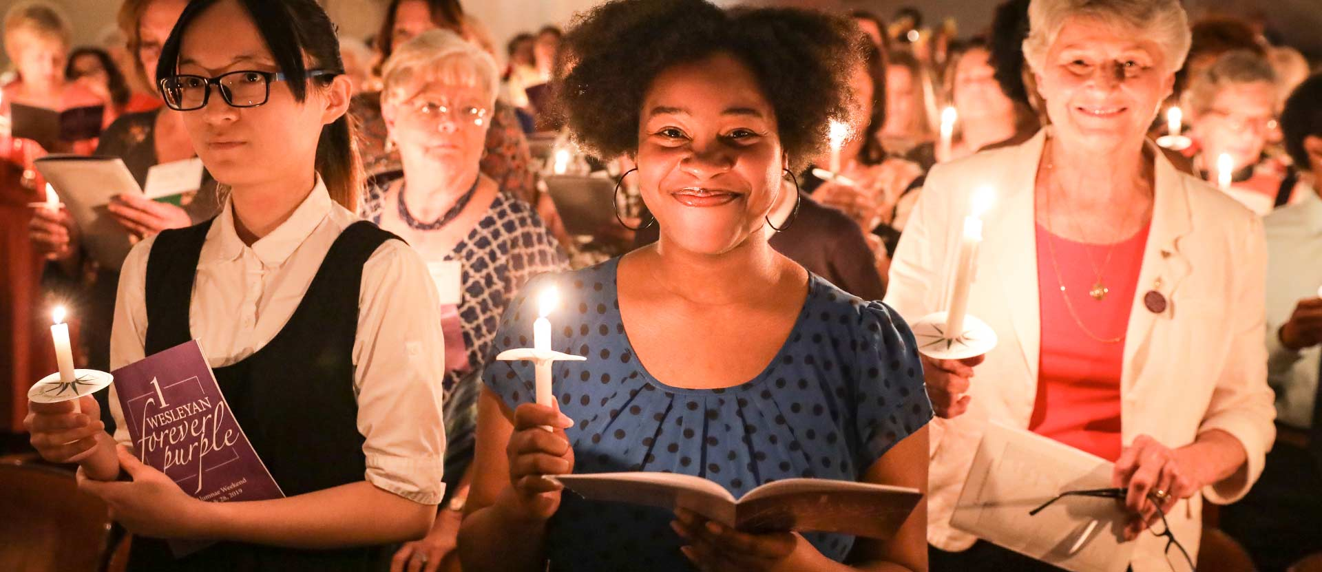 Alumnae smile at the camera holding candles.