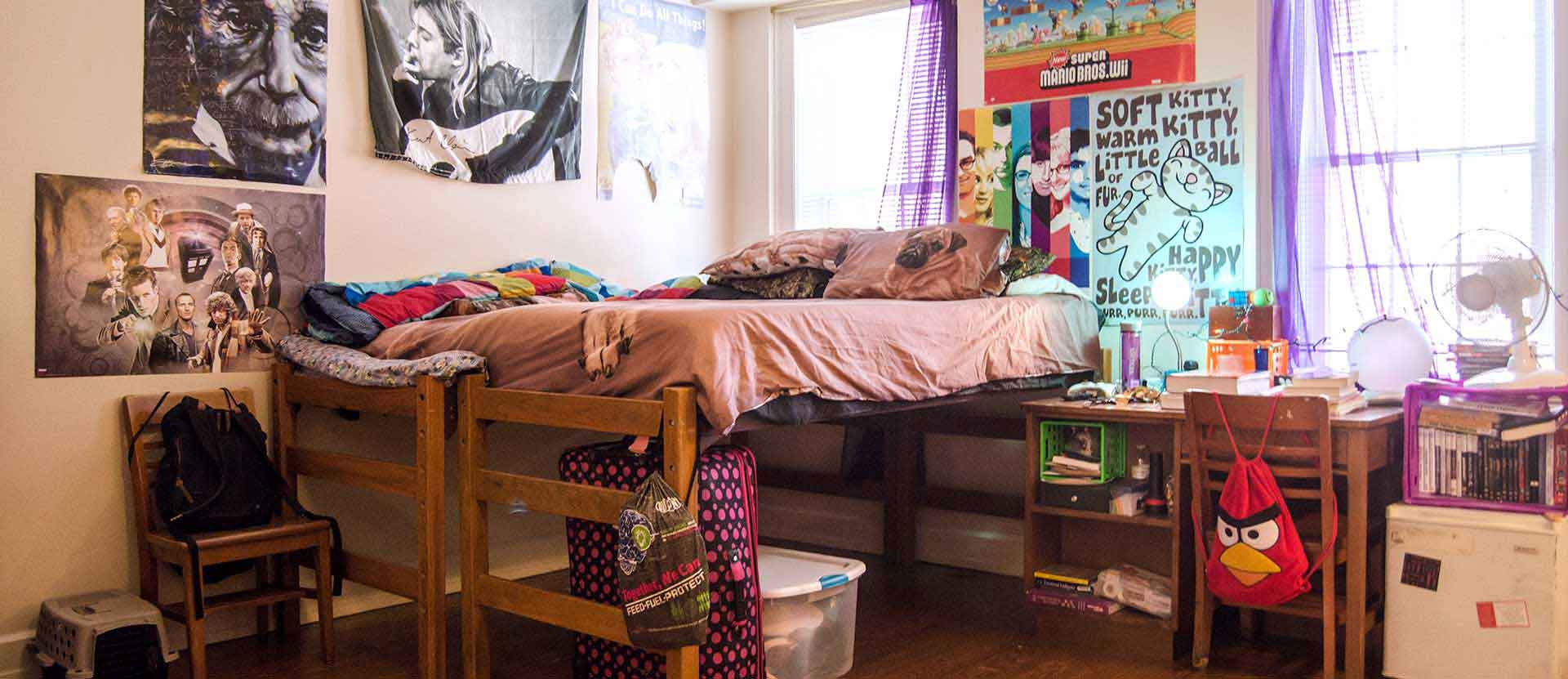 dorm room with bed and posters on the wall