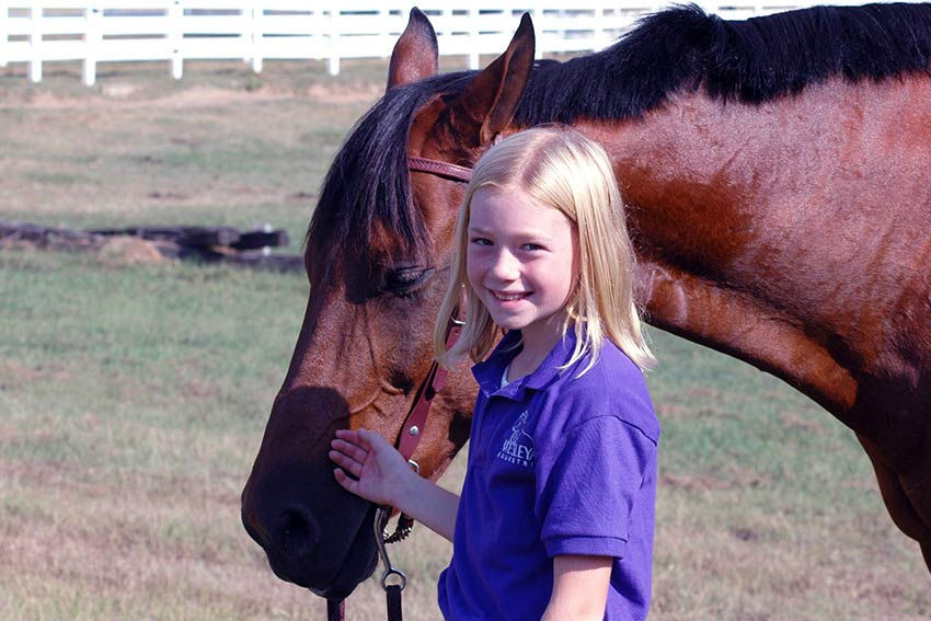 Young girl standing with horse