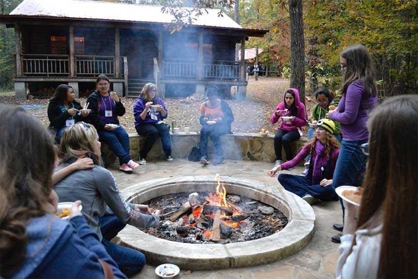 People sit around the firepit with the cabin int he background.