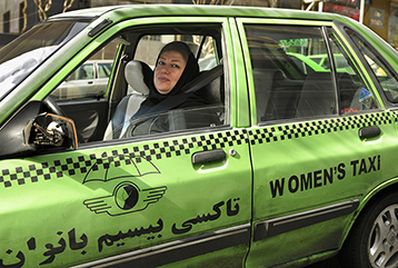 Picture of woman driving a taxi car.