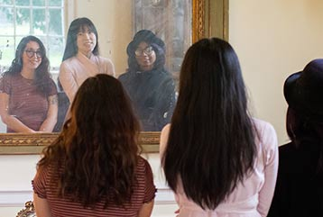 Three students look into the mirror and see their reflections.