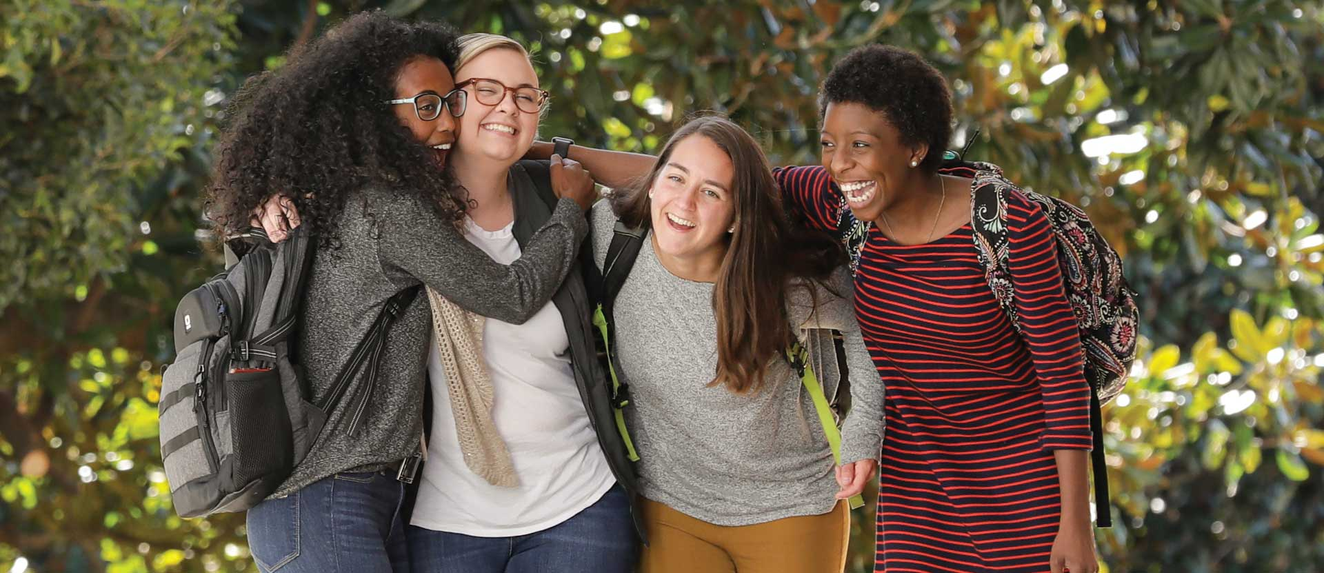 Four students laugh and hug while walking outside.