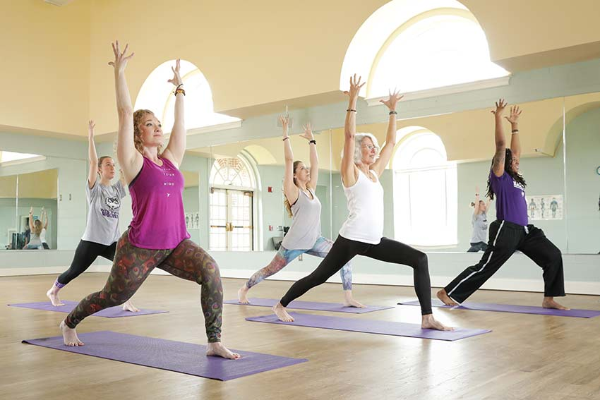 Five women in yoga class, stretching arms to sky.